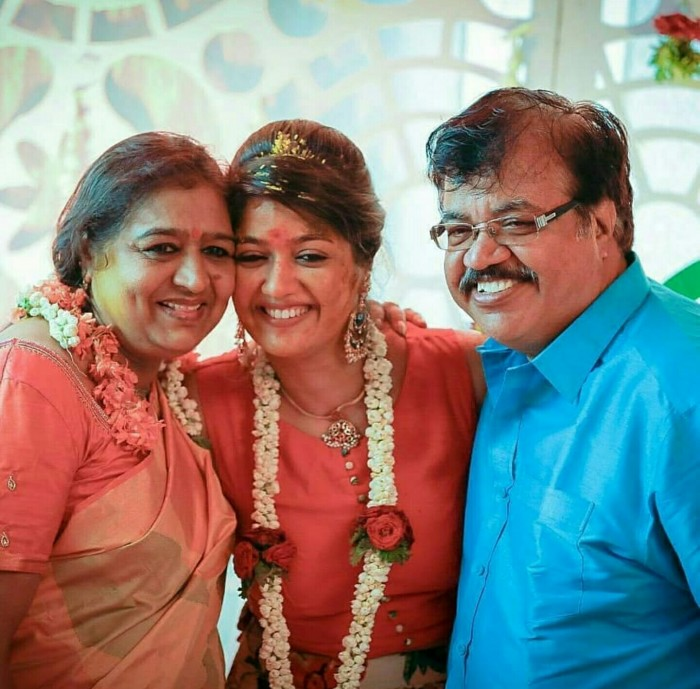 Meghana is all happy as she poses for with her mom and dad.